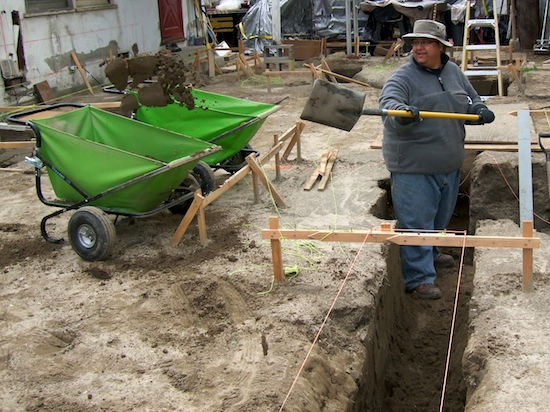 excavation worker moving earth into two wheelbarrows
